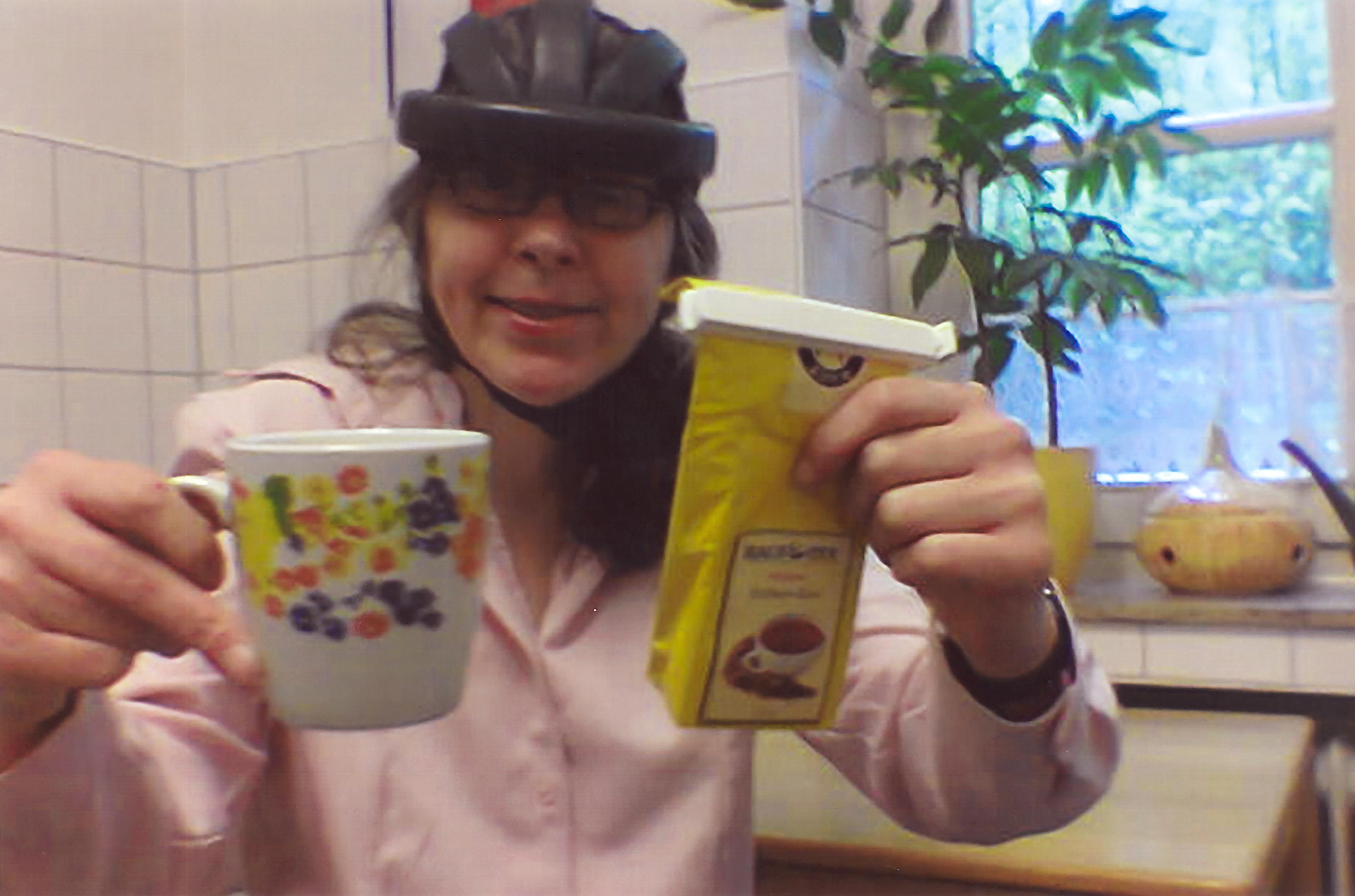 Frau K. zeigt ihre neue Tasse und das Päckchen Tee.